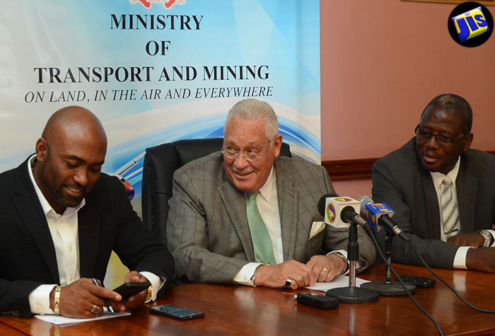 Transport and Mining Minister, Hon. Mike Henry (centre), consults with Science, Energy and Technology Minister, Dr. the Hon. Andrew Wheatley (left), during a media briefing at the Transport Ministry's offices in St. Andrew, on July 28. At right is Permanent Secretary in the Mining Ministry, Dr. Alwin Hales.
