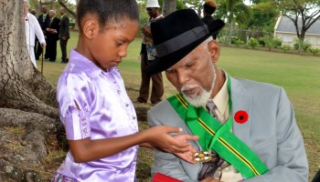 Young Salome Dennis (left), admires her grandfather, Senator Keith Desmond Knight's insignia, after he was conferred with the Order of Jamaica (OJ) during the Ceremony of Investiture and presentation of National Honours and Awards at King's House in St. Andrew, today (October  20). At this year's function, a total of 233 Jamaicans were  recognised for their outstanding contributions to nation building through service in various fields. The ceremony was presided over by Governor-General, His Excellency the Most Hon. Sir Patrick Allen.