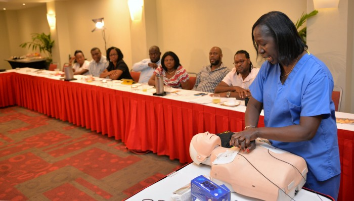 Life Support Instructor in the United States (US), Delores McGregor, demonstrates the cardiopulmonary resuscitation (CPR) procedure to athletic coaches and nurses from five educational institutions, which benefitted from donations of automated external defibrillators (AED) from Team Jamaica Bickle. The presentation of equipment and training session took place yesterday (June 18) at the Hilton Hotel in Montego Bay. The occasion was part of the Diaspora Day of Service, an event of the 6th biennial Jamaica Diaspora Conference held from June 13-18 at the Montego Bay Convention Centre.