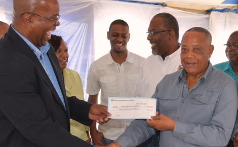 Minister of Agriculture, Labour and Social Securities, Hon. Derrick Kellier, (Right) presents a cheque valued at $27 million representing government's grant funding of the Sweet River Abattoir Agro-Park to Managing Director of the facility, Valdence Gifford during the launching of the facility which is near completion. This represented the 9th agro park to be established by the Ministry of Agriculture and Fisheries across Jamaica. The facility was established through Public/Private partnership at a cost of $292 million.