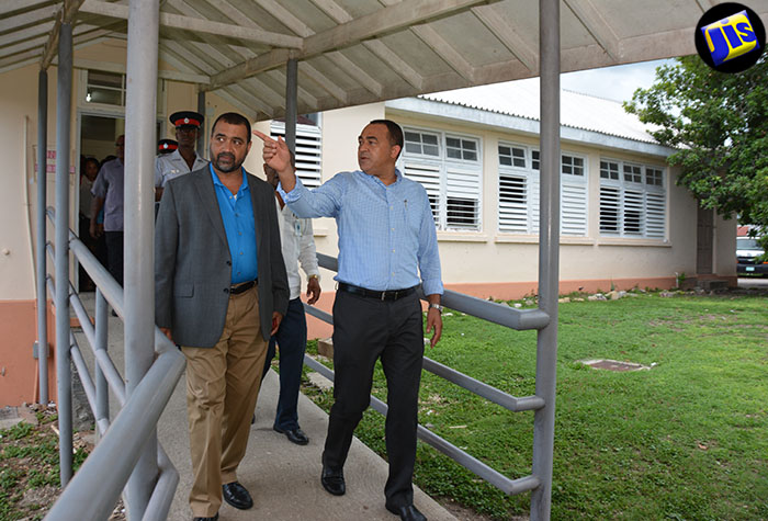 Minister of Health, Dr. the Hon. Christopher Tufton (right), points out something of interest to Acting Chief Medical Officer in the Ministry, Dr. Winston De La Haye, during a recent tour of the Black River Hospital in St. Elizabeth.