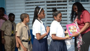 Mayor of Kingston, Senator Angela Brown Burke (right), presents Grade Six Achievement Test (GSAT) workbooks to students of the Rollington Town Primary School in Kingston on Friday, September 19, during a handing over ceremony at the institution.