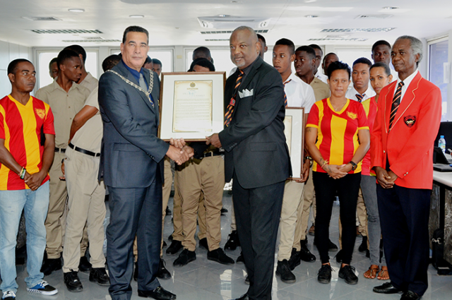 Mayor of Montego Bay and Chairman of the St. James Municipal Corporation, Councillor Homer Davis (fourth left), presents a citation to Dr. Dean Weatherly, coach of the winning 2016 Cornwall College DaCosta Cup football team on January 12. Mayor Davis also presented a citation to Jamario Hines, captain of the football squad on behalf of the team. Looking on are members of the football team and the managers.