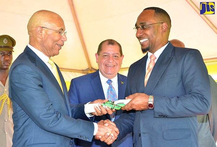 Governor-General, His Excellency the Most Hon. Sir Patrick Allen (left), accepts the Citation for civil servants who were honoured for serving 25 years and more from President of the Jamaica Civil Service Association, O'Neal Grant (right). Occasion was Jamaica Civil Service Long Service Awards ceremony, held on November 30, at King's House, in St. Andrew. At centre is Minister of Finance and the Public Service, Hon. Audley Shaw.