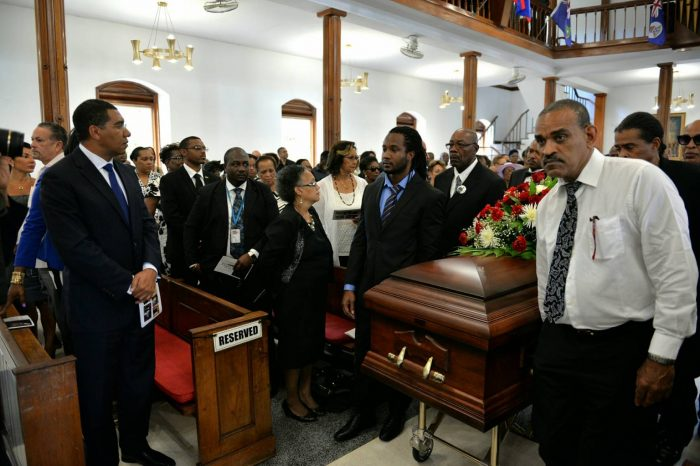 Prime Minister, the Most Hon. Andrew Holness (left), observes as pall-bearers take the casket of the late realist painter Cecil Cooper from the Chapel at the Mona Campus of the University of the West Indies, on September 28, following the Thanksgiving Service.
