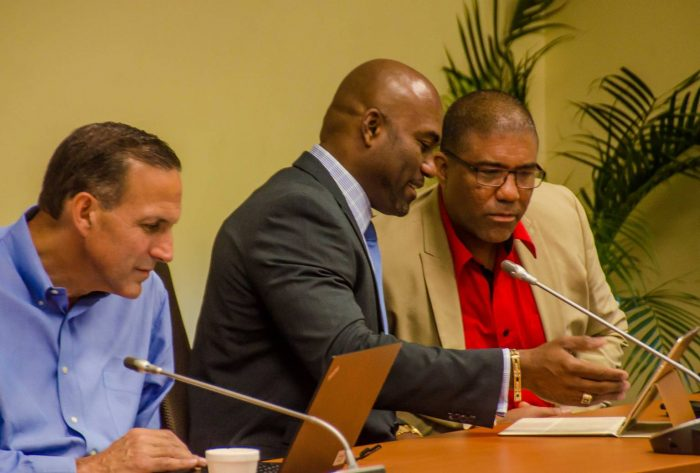 Science, Energy and Technology Minister, Dr. the Hon. Andrew Wheatley (centre), conversing with Jamaica Computer Society (JCS) President, Sheldon Powe (right), during the JCS' symposium at the University of the West Indies' Regional Headquarters in Mona, St. Andrew, on Friday, June 9. Dr. Wheatley was guest speaker at the forum, which was held under the theme: 'The Future of IT Jobs'. Also pictured is Executive Partner of United States-based information technology research and advisory firm, Gartner, Inc., Stephen Bozzo, who was one of the guest presenters.