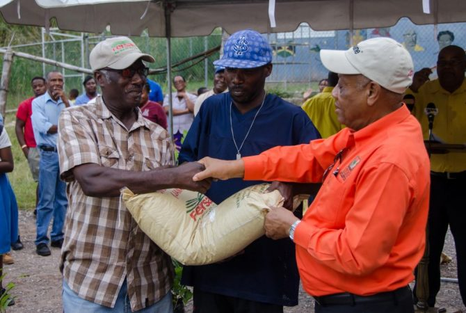 Agriculture and Fisheries Minister, Hon. Derrick Kellier (right), hands over a bag of fertilizer to farmer, Ernest Dennis (left), following a tour of several farms in East Rural St. Andrew which were affected by fires in May 2015. The provision is part of the Government's $25 million mitigation and rehabilitation intervention. At centre is Rural Agricultural Development Authority (RADA) officer, Ricardo Thomas.