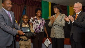 Prime Minister, the Most Hon. Portia Simpson (2nd right); and Minister of Education, Hon. Rev. Ronald Thwaites (right); applaud as Minister of Science, Technology, Energy and Mining, Hon. Phillip Paulwell (left), presents a tablet computer to Haile Selassie High School student, Tarique Salmon. Occasion was the handing over of tablets to students of the school on September 29, under the Government's $1.4 billion Tablets in Schools pilot project.  Tarique's mother, Vinnel Lawson (2nd left), also shares the moment.