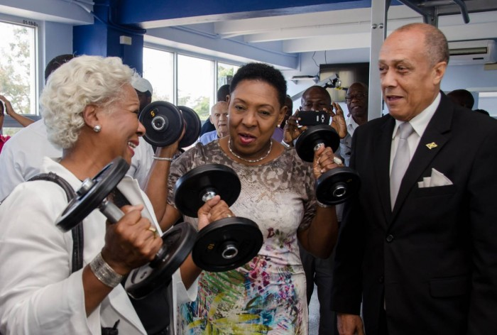 Minister of Entertainment, Sport, Culture and  Gender Affairs, Hon. Olivia 'Babsy' Grange  (centre), tries out the weights at the National Health Fund/Jamaica Cricket Association (JCA) wellness centre, which was officially opened at  Sabina Park,  today (March 17).  Others (from left) are:  Project Manager, Culture, Health, Arts, Sports and Education (CHASE) Fund, Paulette Mitchell and former national football player, Ali McNab.