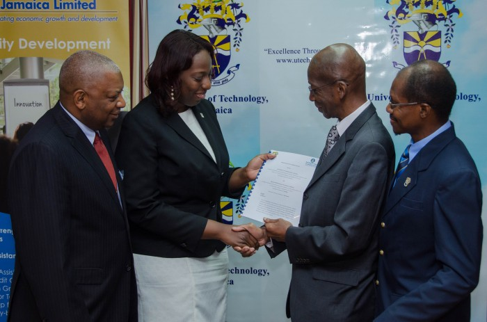 Acting President, University of Technology (UTech), Ambassador the Hon. Burchell Whiteman (second right) and General Manager, Strategic Services, Development Bank of Jamaica (DBJ), Claudine Tracey (second left), exchange copies of a Memorandum of Understanding (MoU) they signed, which will see the development of U-Touch 2, a multimedia software designed to enhance the learning process for deaf and hearing impaired students. The signing took place today (January 14), at UTech's Papine campus in St. Andrew. Also pictured (from left) are: Dean, College of Business and Management, UTech, Dr. Paul Golding; and Deputy President, Professor Colin Gyles.