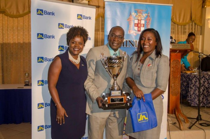 Minister of Education, Youth and Information, Senator the Hon. Ruel Reid (centre), presents teacher at the Crescent Primary School in St. Catherine, Neisha Grant Lawrence (right), with the Mathematics Teacher of the Year trophy in March. At left is Senior Manager, Learning Development Culture, Jamaica National Group, Dr. Renée Rattray.