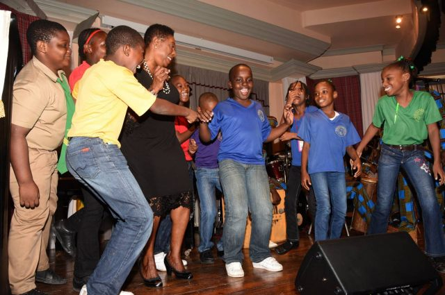 Minister of Culture, Gender, Entertainment and Sport, Hon. Olivia Grange (third left) dances with students of Duhaney Park Primary during their performance at the Heritage Fest at the Institute of Jamaica in downtown Kingston on October 27.