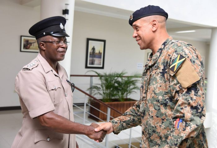 Jamaica Defence Force (JDF) Legal Officer, Captain Michael Deans (right), greets Jamaica Constabulary Force (JCF) Deputy Superintendent of Police Errol Thompson, at Friday's (July 21) penultimate day of the five-day Zones of Special Operations (ZoSo) Human Rights and Social Development training,  at the JDF Directorate of Training and Doctrine, Up Park Camp, Kingston.