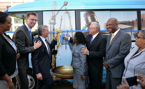 Justice Minister, Hon. Delroy Chuck (second right), cuts the ribbon to launch the Legal Aid bus, at the Ministry on Constant Spring Road, on January 13. He is assisted by Legal Aid Council Chairperson, Jacqueline Cummings (right) and Head of Cooperation at the Canadian High Commission, Walter Bernyck (third left). Others (from left) are Social Marketing Coordinator of the Citizen Security and Justice Programme, Jacqueline Nephew; Country Representative of the United Kingdom's Department for International Development (DFID), David Osbourne; Executive Director of the Legal Aid Council, Hugh Faulkner and Permanent Secretary in the Ministry of Justice, Carol Palmer.
