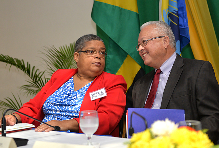 Justice Minister, Hon. Delroy Chuck (right), shares pleasantries with Permanent Secretary, Carol Palmer, during the Ministry's Eighth International Restorative Justice Conference, which was held at The Jamaica Pegasus hotel in New Kingston on Friday, February 10, under the theme: 'Building Restorative Communities in Faith Groups, Schools and Workplaces'.
