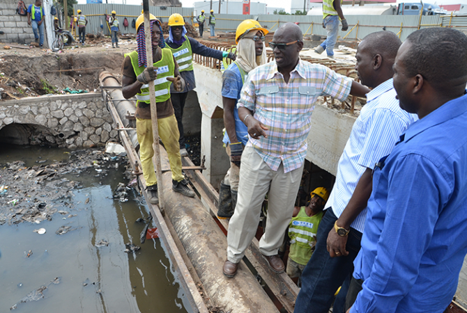 Local Government and Community Development Minister, Hon. Desmond McKenzie (3rd right), converses with workmen involved in the road expansion project by the National Works Agency (NWA) on Marcus Garvey Drive in Kingston, during a tour of the area on Friday, September 16.