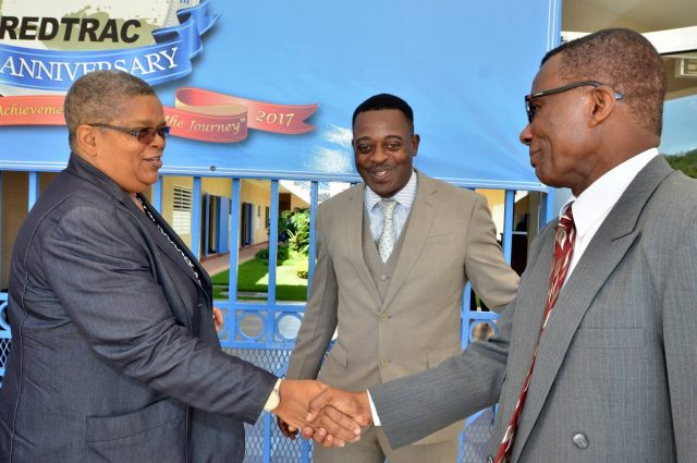 Permanent Secretary in the Ministry of Justice, Carol Palmer (left), greets Director/Principal of the Caribbean Regional Drug Law Enforcement Training Centre (REDTRAC), Major George Benson (right), during Friday's (June 30) graduation ceremony and luncheon for local and regional law enforcement officials who participated in a two-week Trafficking in Persons course at REDTRAC in Twickenham Park, St. Catherine. Looking on is Deputy Superintendent of Police, Carl Berry.