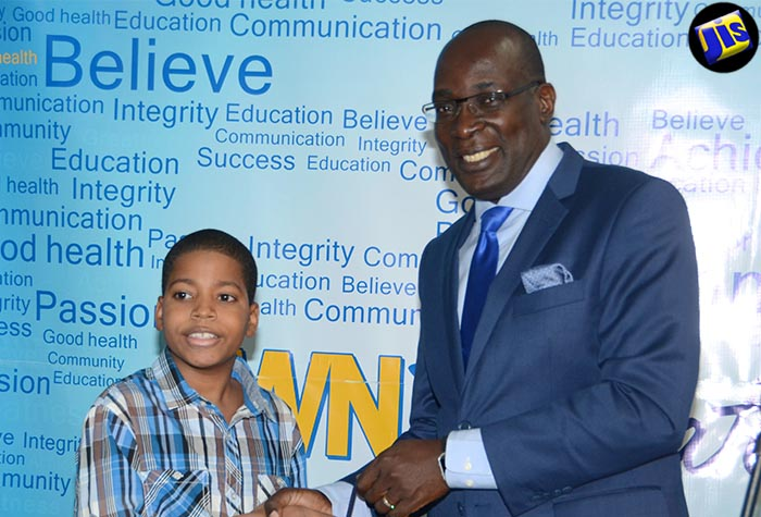 Minister of Education, Youth and Information, Senator the Hon. Ruel Reid (right), is presented with a token on behalf of  J. Wray & Nephew (JWN) Foundation, by scholarship recipient Lenworth Hydol, during the Foundation's annual awards ceremony, held on August 24 at the J. Wray Nephew Limited's corporate offices, in New Kingston.
