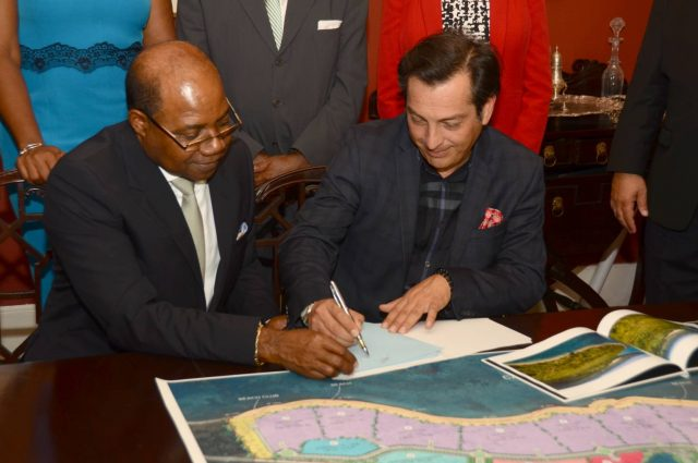 Minister of Tourism, Hon. Edmund Bartlett (Left), signs contract with Karisma Hotel and Resorts' Vice-President of Corporate Affairs & Business Development, Ruben Becerra (Right) on June 14 at Devon House.