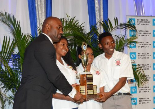 Minister of Science, Energy and Technology, Dr. the Hon. Andrew Wheatley (left), presents the winning trophy to Campion College team members (from second left), Jenine Shepherd, Jillian Edwards and Maliic Graham, who copped first place in the Petroleum Corporation of Jamaica (PCJ) Schools Energy Programme competition, at the awards ceremony on June 24, at the Knutsford Court Hotel, in New Kingston.