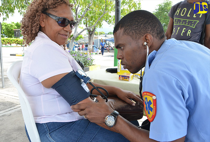 Emergency Medical Technician, Corporal Mikhail Clarke (right), checks the blood pressure of  Sheron Nelson, at the Jamaica Fire Brigade's (JFB) Fire Safety Awareness Week exposition held on October 26 at Mandela Park in St. Andrew.