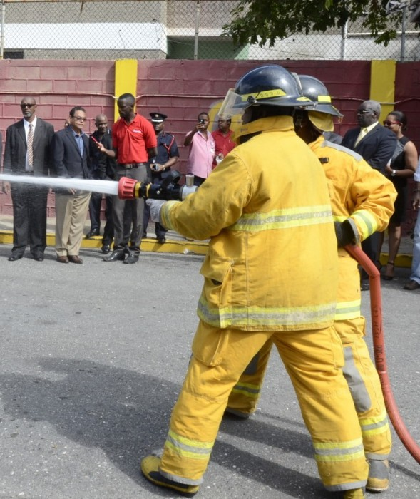 Firefighter: Firefighters demonstrate the capabilities of one of three new fire units, which were handed over to the Jamaica Fire Brigade (JFB), during a ceremony on February 4, at the York Park Fire Station, Orange Street, Kingston.
