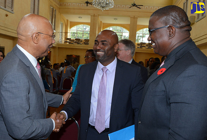 Governor-General, His Excellency the Most Hon. Sir Patrick Allen, exchanges a warm handshake with Minister of Science, Energy and Technology, Dr. the Hon. Andrew Wheatley at the Proclamation ceremony for Science and Technology Month held on October 25 at King's House. Looking on is Executive Director of the Scientific Research Council (SRC), Dr. Cliff Riley. The month will be observed in November under the theme 'Science, Technology and Innovation: Stimuli for Health, Wealth and Wellness'.