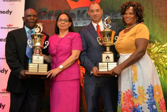 Minister of Labour and Social Security, Hon. Shahine Robinson (second left) and Group Chief Executive Officer for GraceKennedy Limited, Senator Don Wehby (third left), present trophies to winners of the GraceKennedy/Heather Little-White Household Worker of the Year Awards, Anthony Houston (left) and Cherilene Williams-Case (right) during the awards ceremony, held on October 5 at The Jamaica Pegasus hotel in Kingston.
