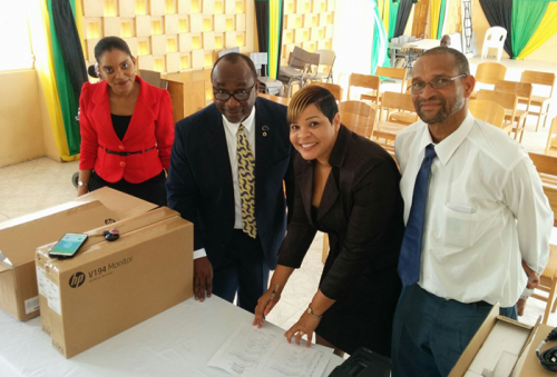 Chairman of the Universal Service Fund (USF), Robert Lawrence (second left), displays computers (on table), which he handed over to the Golden Age Home recently. Others (from left) are Assistant General Manager of the Golden Age Home, Mishka Townsend-Brown; General Manager of the Golden Age Home, Laurette Adams-Thomas and Acting Chief Executive Officer of the USF, Everold Simms.