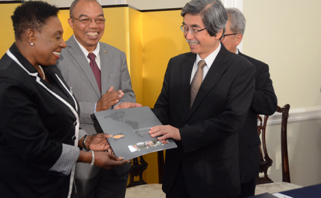 Minister of Culture, Gender, Entertainment and Sport, Hon. Olivia Grange (left), presents Japan's Ambassador to Jamaica, His Excellency Masanori Nakano (2nd right), with a souvenir publication on Jamaica during Thursday's (May 5) signing of the Friendship Exchange Agreement between the Jamaica Athletics Administrative Association (JAAA), and Tottori Athletic Association (TAA) in Japan. The signing took place at the Ambassador's residence in St. Andrew. Sharing the moment (from 2nd left) are: JAAA President, Dr. Warren Blake; and TAA Chairman, Shinichi Hamasaki (partly hidden).