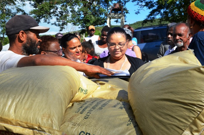 Minister of Information, Senator the Hon. Sandrea Falconer (right), presents a 400-gallon water tank to Pastor of the Queensbury Missionary Church, in South West St. Elizabeth, Laurette Ellis (left), on December 1, as part of her outreach project for the community in which she was born. The Minister presented black water tanks, fertilizer and vegetable seeds to assist farmers with replanting, following the prolonged drought.