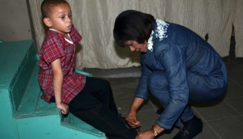 Prime Minister, the Most Hon. Portia Simpson (right),  ties the shoe lace of little John Spence, a student of the Kidz Palace Nursery and Educational Limited, after he and other students of the school performed at the National Land Agency's (NLA) land titling ceremony in Montego Bay, St. James on Friday (May 22). The Prime Minister met with the children after they performed.