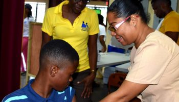 Nurse Andrea James (right) of the Kingston and St. Andrew Health Department, applies pressure to the upper arm of 14-year old Garfield James, after administering a vaccine. Occasion was a Children's Health and Wellness Fair staged by the National Child Month Committee (NCMC) on May 28 at the Wolmer's Boys School, Kingston. Looking on is NCMC member, Judith Hunter.