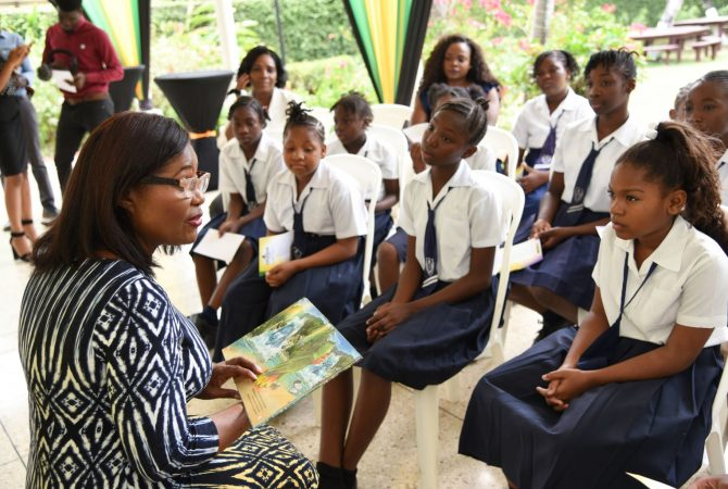 Her Excellency, the Most Hon. Lady Allen (left), reads to children at King's House on Friday (April 27), after launching the 2018 Western Union's I Pledge (Reading) Programme.