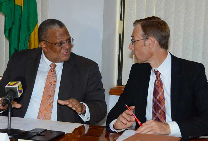 Minister of Finance and Planning, Dr. the Hon. Peter Phillips (left), is in conversation with International Monetary Fund (IMF) mission chief to Jamaica, Jan Kees Martijn, shortly before the start of a post-IMF review press conference today, at the Ministry's National Heroes Circle offices in Kingston.