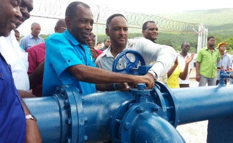 Minister without Portfolio in the Ministry of Industry, Commerce, Agriculture and Fisheries, Hon. J.C. Hutchinson (3rd left), and Jamaica Social Investment Fund Managing Director, Omar Sweeney (right, foreground), symbolically turn on the new $30.3 million pump at the New Forest/Duff House Agro Park in south Manchester, which was commissioned into service on June 29.