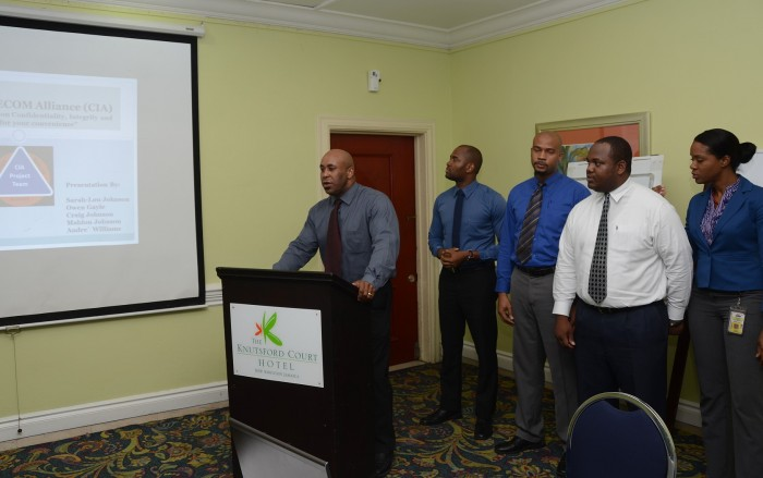 Participant in the just concluded one-week ISO 27001-information security management system workshop and Jamaica Customs Agency (JCA) officer, Andre Williams (left), makes his group's presentation, during the closing session at the Knutsford Court Hotel, New Kingston. Listening keenly, from 2nd left are group members:  Craig Johnson, Mahlon Johnson, Owen Gayle and Sarah-Lou Johnson. The workshop was conducted by Educentres Information Services Limited for government officers from several departments and agencies.