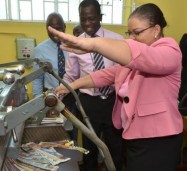 Minister with Responsibility for Information, Senator the Hon. Sandrea Falconer (right, foreground), tries her hand at using a guillotine on display at the offices of the Jamaica Archives and Records Department (JARD) in Spanish Town, St. Catherine, during her tour of the agency on June 27.The tour followed her unveiling of two Plaques of Inscription, awarded to JARD by UNESCO, for three of Jamaica's historical collections, being maintained by JARD, which are included on UNESCO's Memory of the World Register. Looking on are: JARD Archives Restorer, Mekko Walker (2nd left), and other agency members of staff.