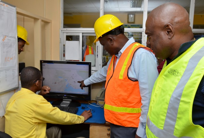 Managing Director of the Jamaica Urban Transit Company (JUTC), Colin Campbell (right), looks on as Manager of the JUTC's Spanish Town Depot, Neville Francis (second right), highlights aspects of the company's Automatic Vehicle Locator (AVL) tracking system, which is to be fully rolled out on Monday, September 1. At left is the JUTC's Information Technology Manager, Brian Tulloch.
