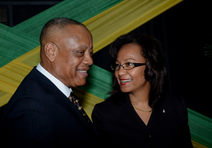 Minister of Agriculture, Labour and Social Security, Hon. Derrick Kellier (left), having a light conversation with newly appointed Permanent Secretary in the Ministry, Collette Roberts-Risden, prior to the start of a send-off ceremony for the first batch of workers for 2015 under the Ministry's Overseas Employment Programme, held at the Overseas Employment Services Centre in Kingston, today (January 6).