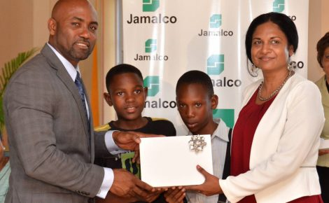 Minister of Energy, Science, and Technology, Hon. Dr. Andrew Wheatley (left), presents a tablet computer to teacher at the Hayes Primary School in Clarendon, Tracy-Ann Williams (right); and students Willward Robinson (2nd left); and Rahiem Cunningham. Occasion was a tablet handing over ceremony staged by Jamalco on March 23, at the Wembley Centre of Excellence in Hayes, Clarendon.