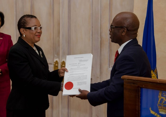 Deputy Governor-General, the Hon. Steadman Fuller (right), presents the instrument of office to Miss Justice Carol Edwards, who will serve as a Judge of the Appeal Court. The occasion was the swearing in of judges on March 29 at King's House.