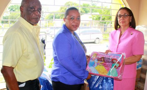 Minister of Labour and Social Security, Hon. Shahine Robinson (right), hands over relief supplies to Chief Executive Officer of the Child Protection and Family Services Agency (CPFSA), Rosalee Gage-Grey, for fire victims of the Walkers Place of Safety. The presentation was made at the Maxfield Park Children's Home in Kingston on Friday (Jan. 19). At left is Manager of the Maxfield Park Children's Home, Winston Bowen.