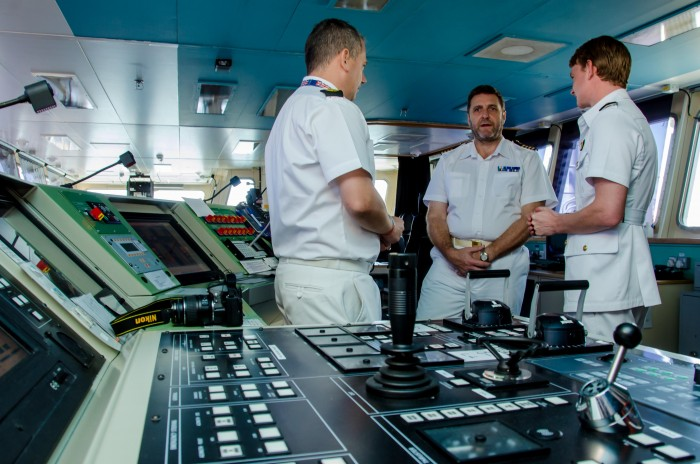 Commanding Officer of Royal Fleet Auxiliary (RFA) Lyme Bay, Captain Paul Minter (centre), in discussion with Assistant to the British Defense Advisor, Chief Petty Officer Allan Hurley (left), and Media Officer, Lt. Max Cosby, during a media tour of the British naval vessel, which is docked at the Kingston Wharves.