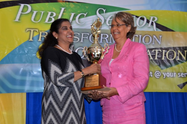 Chairman of the Public Sector Transformation Steering Committee, Patricia Francis (right), presents the Prime Minister's Trophy and $300,000 cash prize to Administrator General and Chief Executive Officer (CEO) of the Administrator General's Department, Lona Brown. The agency copped the award for Best Customer Service Entity (Single Location) in the Public Sector Customer Service Competition (PSCSC). The awards ceremony was held last Friday (October 9) in Kingston.