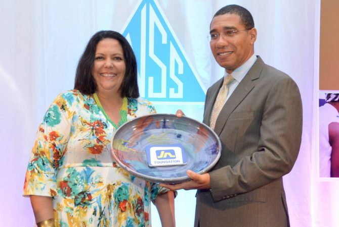 Prime Minister, the Most Hon. Andrew Holness, accepts a token from Chair of the Council of Voluntary Social Services (CVSS), Saffery Brown, at the CVSS 2016 National Volunteer Awards Banquet, held at The Jamaica Pegasus hotel in Kingston, on December 8.