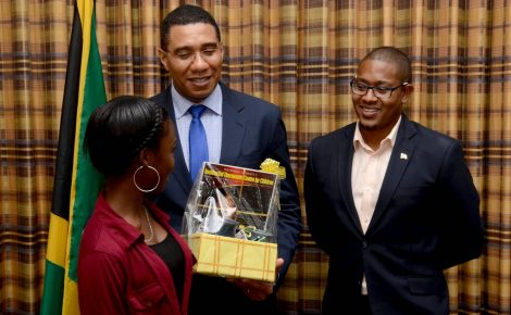 Prime Minister, the Most Hon. Andrew Holness (centre), accepts a gift from one of 18 wards of the State, who visited the Office of the Prime Minister on Friday, May 20. At right is Ministry of Education, Youth and Information, Hon. Floyd Green. The visit was part of a Child Month educational excursion in the Corporate Area by the South East Region of the Child Development Agency (CDA).