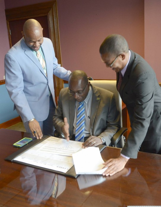 Education, Youth and Information Minister, Senator, the Hon. Ruel Reid (seated), goes over his schedule with Permanent Secretary in the Ministry, Dr. Maurice Smith (left), when he arrived for his first working day at the Ministry, at National Heroes Circle, today (March 8). At right is State Minister in the Ministry, Senator the Hon. Floyd Green.