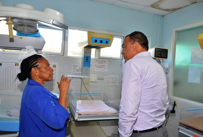 Minister of Health, Hon. Dr. Christopher Tufton (right), listens intently to Director of Nursing Services at the Spanish Town Hospital, Sherleen Marshal Davis, as she explains how babies are cared for in the nursery. Occasion was a tour of the hospital in St. Catherine on June 9.