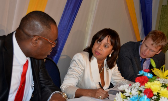 Minister of State in the Ministry of Industry, Investment and Commerce, Hon. Sharon Ffolkes-Abrahams (centre), in conversation with Executive Director of the HEART Trust/NTA, Dr. Wayne Wesley (left), at an economic growth symposium held today (October 1), at the Knutsford Court Hotel, in New Kingston, and organized by the HEART Trust/NTA. At right is Research Fellow at the United States based Harvard University, Dr. Brad Cunningham.